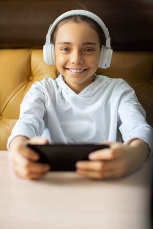 Vertical photo of a teenage girl wearing white headphones playing an online game on her smartphone. She smiles and looks into the camera