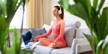 Young woman meditating at home. She use a tutorial from the Internet. Format photo 1x2. Standard-Bild