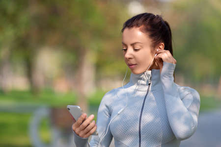 Photo of a young woman jogging. She sets up the music on her phone for a good jogging mood. Standard-Bild