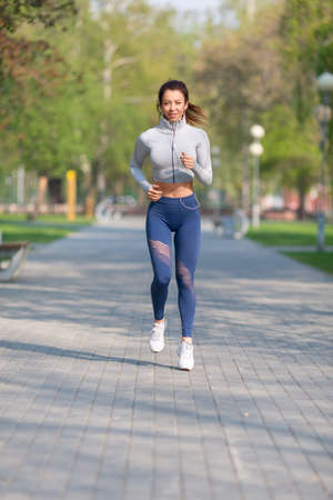 Full-length photo of a young woman runs in the city park. Concept of keeping fit and healthy lifestyle.