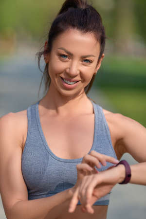 Close-up photo of a woman. She smiles and checks her pulse after the race with her smartwatch. The concept of a healthy lifestyle and keeping fit in a fit shape.