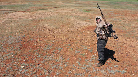 Photo of a soldier sniper in the desert. He stands, looks at the camera and shows his rifle. Standard-Bild