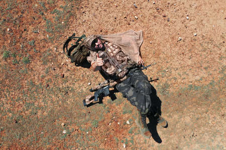 Top view - a soldier sniper while resting. He lies on the red-hot desert ground and rests. He shows his thumbs up to the camera.