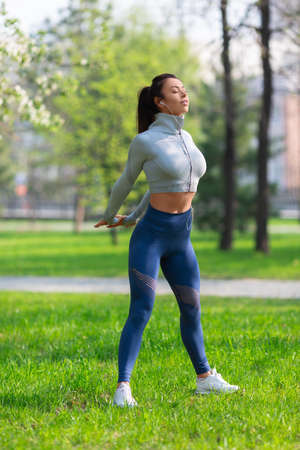 Vertical photo of a woman stretching body - warming up before running or working out. Female runner stretching arms before running at morning.