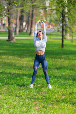 Young woman stretching body - warming up before running or working out. Female runner stretching arms before running at morning. Vertical photo.