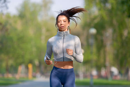 Young woman running in the city park in early morning. Attractive looking woman keeping fit and healthy. Close-up photo.
