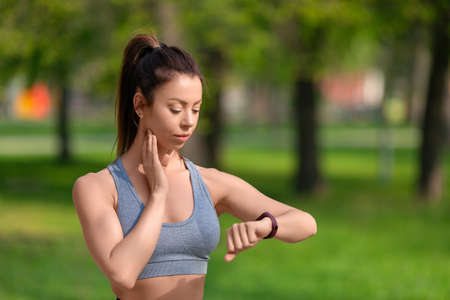 Healthy lifestyle concept - woman checks her pulse after jogging workout in the park.