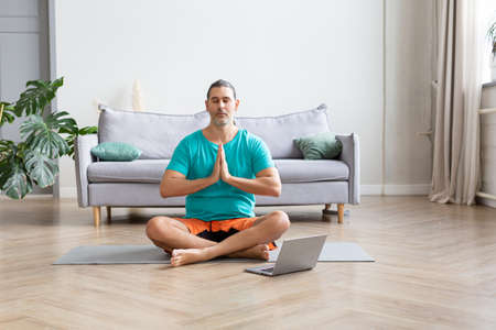 Photo of a man meditates in front of a laptop monitor. He sits in the lotus position in home decor. Prayer pose.