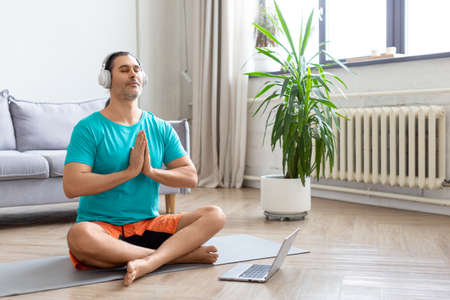 A man meditates in front of a laptop monitor. He sits in the lotus position in home decor. Prayer pose.