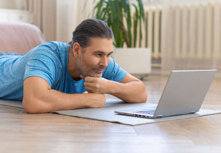 Middle-aged man at home in front of laptop during online video meeting with friends. 版權商用圖片