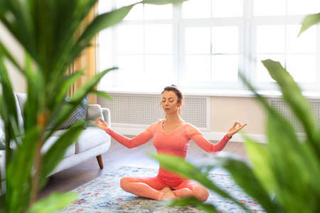 Young woman meditates at home. Mental health concept.