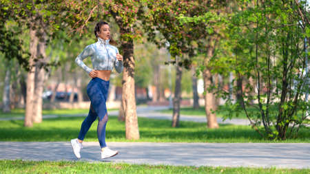 Full length photo of a woman running in park in early morning. Attractive looking woman keeping fit and healthy. Format 16x9.