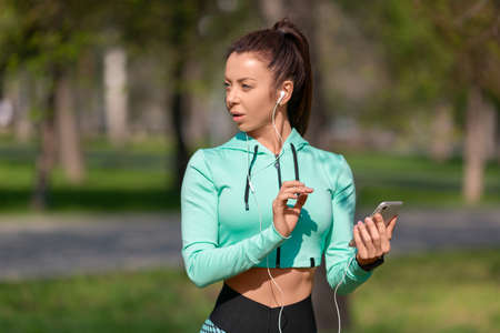 Photo of a young woman with a smartphone. She chooses jogging music and looking by side.