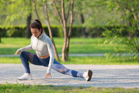 Full-length photo of a woman during outdoor workout. She stretches the leg muscles and warms up before jogging workout.