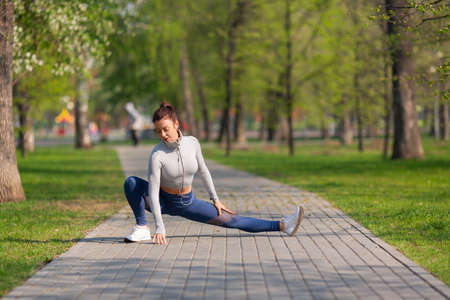 Full-length photo of a woman during stretchig workout in city park. She stretches the leg muscles and warms up before jogging workout.