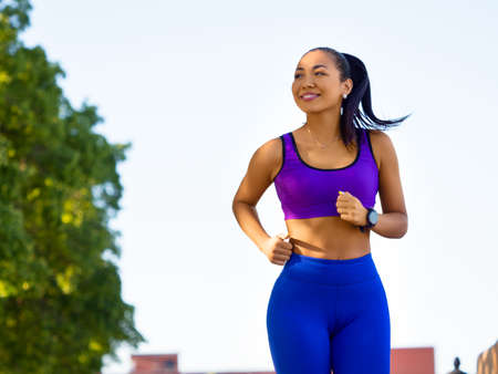 Asian woman running early in the morning. Attractive looking woman keeping fit and healthy.
