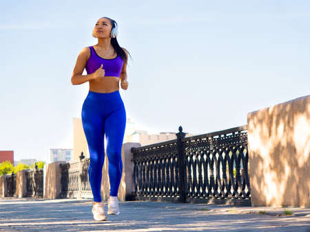 Asian woman running in park in early morning. Attractive looking woman keeping fit and healthy.
