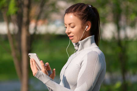 Photo of a young woman with a smartphone. She chooses jogging music.