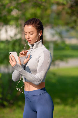 Vertical photoof a young woman with a smartphone. She chooses jogging music.