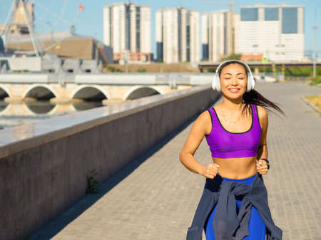 Asian woman jogging early in the morning. Attractive looking woman keeping fit and healthy.