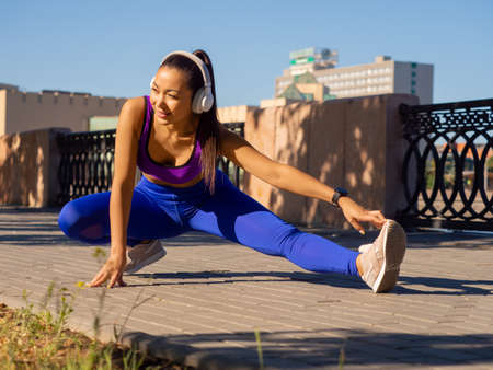 Full-length photo of a woman during outdoor workout. She stretching legs and warming up before jogging workout.