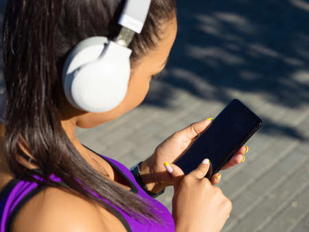 Young Asian girl in white headphones chooses music for jogging in a mobile application.