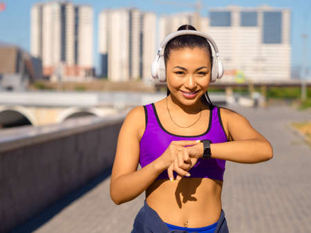 Young asian woman in white headphones checks her pulse with smartwatch during the race, smiling and looking at camera. Standard-Bild