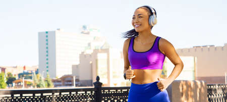 Young Asian girl in white headphones runs early in the morning against the backdrop of the cityscape. Forrmat 20x9.