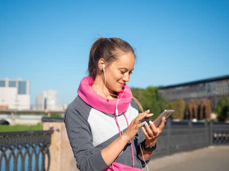 Photo of smiling woman with a smartphone outdoor. She chooses jogging music.
