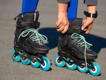 Close-up of an Anonymous Womans Hands Fixing Laces on Roller Blades Before Skating.