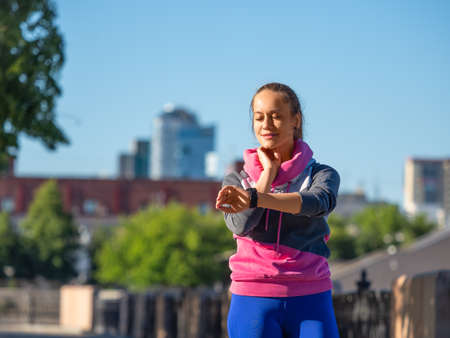 Young woman during the morning jog measures the pulse by checking the watches.