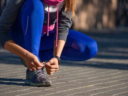 Close-up of a woman tying the laces of her sneakers during her morning run.