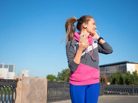 Woman during morning jogging workout. She puts the earpiece in her ear and selects running music. Standard-Bild