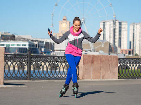 Young woman is rollerblading with a smartphone in her hands and listening to music through headphones. She Moves to the music and enjoys life. Standard-Bild