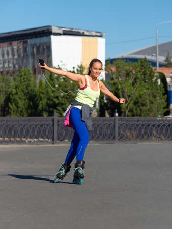 Portrait of a young woman while rollerblading. She listens to music through headphones from her smartphone and enjoys life. Standard-Bild