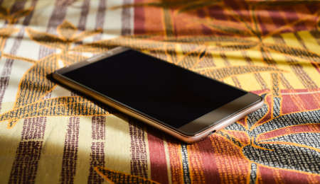 gold smartphone lying on a blanket