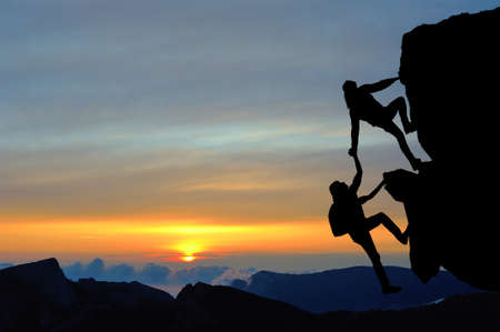 The joint work teamwork of two men travelers help each other on top of a mountain climbing team, a beautiful sunset landscape Foto de archivo