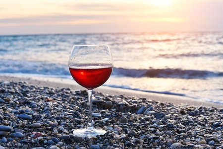 romantic sky: Romantic glass of wine sitting on the beach at colorful sunset, Glass of red wine against sunset, red wine on the sea ocean beach, sky background with clouds Stock Photo