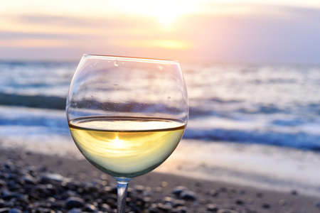 romantic sky: Romantic glass of wine sitting on the beach at colorful sunset Glasses of white wine against sunset, white wine on the sky background with clouds