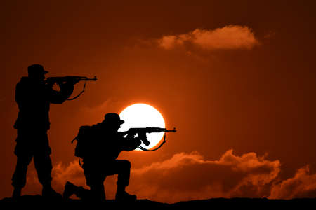 Silhouette of military two soldier or officer with weapons at sunset. shot, holding gun, colorful sky, mountain, background, team Stock Photo