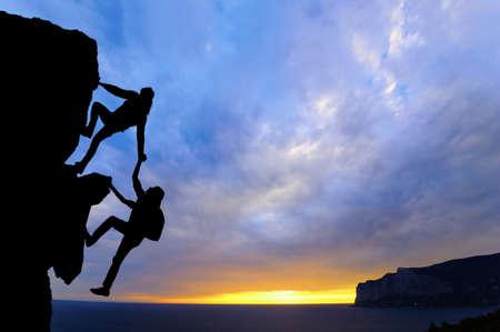 Het gezamenlijke werksamenwerking van twee heren reizigers helpen elkaar op de top van een bergbeklimmingsteam, een prachtig zonsonderganglandschap