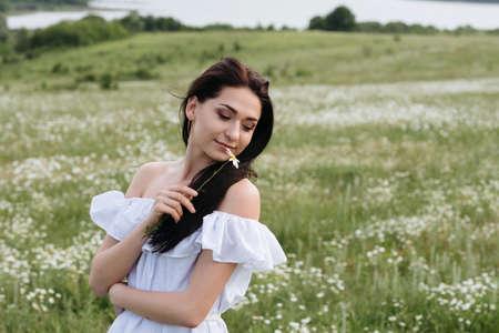 lovely pregnant woman: Portrait of brunette girl in white dress in field of chamomile