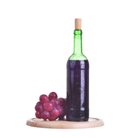 Bottle of red wine and grapes on wooden plate isolated on white
