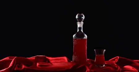 Bottle and glass with red wine on black background with red cloth, satin fabric, silk