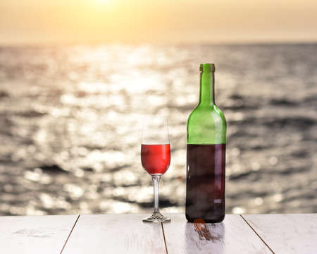 Bottle and glass of red wine on the linen table against the sea or ocean Stok Fotoğraf