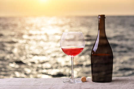 Bottle and glass of red wine on the linen table against the sea or ocean on sunset