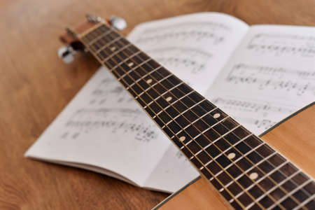 Acoustic guitar with notes of song on a wooden floor. Guitar music note sheet chord