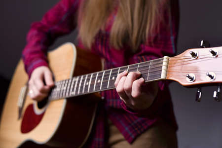 womans hands playing acoustic guitar, close up. Playing acoustic guitar girl or woman with long hair by fingers. finger position on the chord. selective focus image