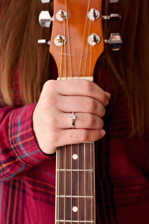Womans girl hand with ring holding a guitar neck chord