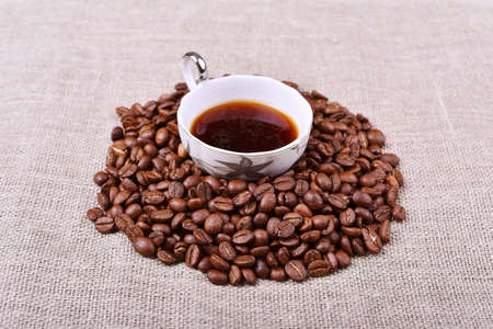 Cup of coffee with coffee beans on linen texture table